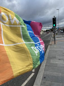 Rainbow Project Flag blowing in the wind showing marathon runners in the distance